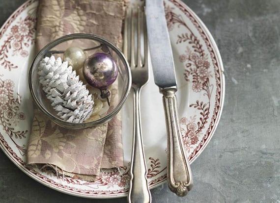 tisch rustikal eindecken zu weihnachten mit silberbesteck, stoffserviere und weihnachtskugel im teller mit blumenmuster