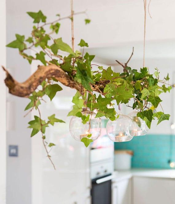 rustikale küchendeko mit zweig, frischem efeu und glaskugeln für teelich als natürliche hängedeko