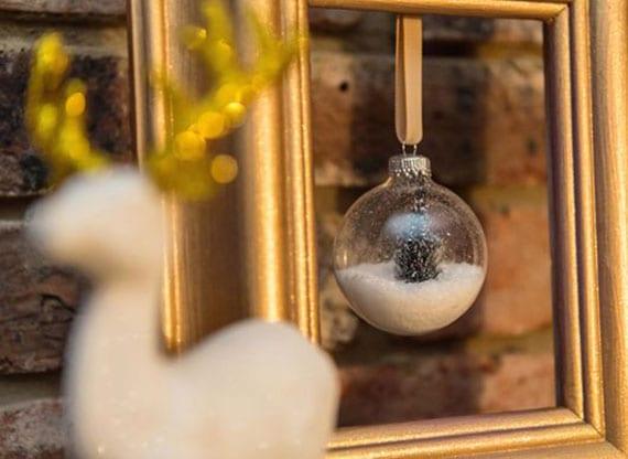 originelle diy weihnachtsdeko mit weißer hirschfigur und glaskugel im goldfarbigem bilderrahmen
