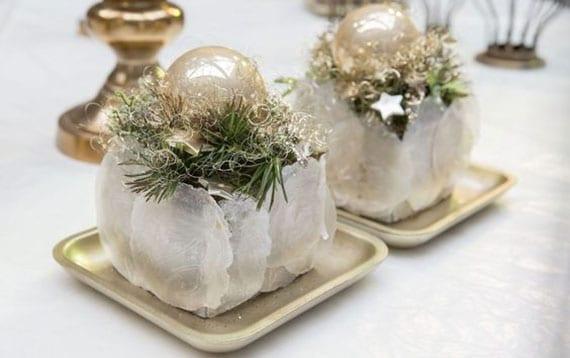 elegante und reizvolle weihnachts-tischdeko mit mini gesteck aus tannengrün und christbaumkugel in edlen goldfarbigen schalen
