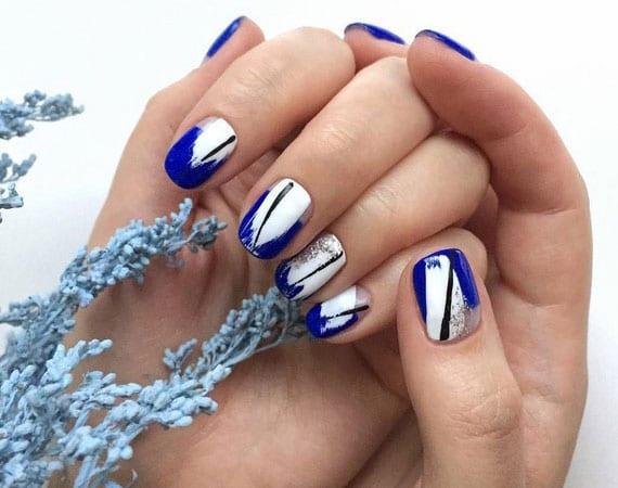 moderne wintermaniküre für kurze nägel in farbkombination vov weiß, blau, schwarz und silber