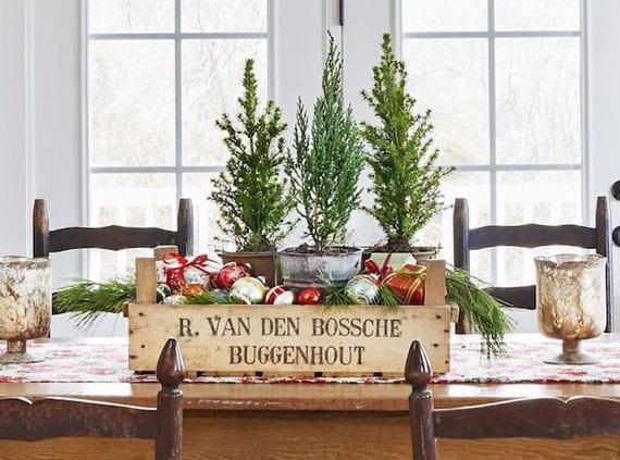klessische weihnachtsdeko idee für den tisch mit christbaumkugeln und tannengrün in verwitterter holzkiste