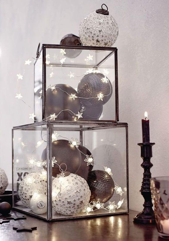 coole weihnachtsdeko in schwaz-weiß mit christbaumkugeln und stern-lichterkette in glasboxen