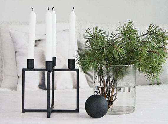 moderne winterdeko im skandinavischen stil mit tannengrün in glasvase, kerzenhalter für vier kerzen und schwarzer christbaumkugel