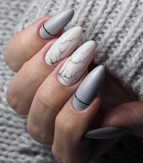 schöne maniküre in grau und weiß mit marmor-design und effektvolle steinchen-deko
