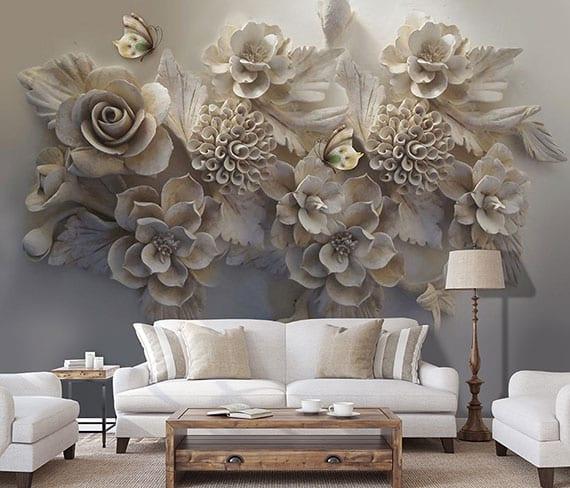 florale 3D wandtapete mit tiefenwirkung als akzentuierende gestaltung einer wand im wohnziimer mit weißen polstersofa und sesseln und rustikalem holzkaffeetisch