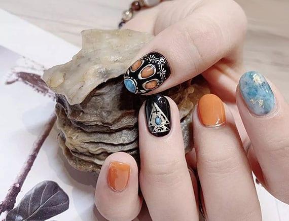 auffällig maniküre kurze nägel_schöne nagelgestaltung in schwarz, orange und blau