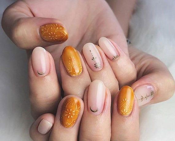nageldesign im boho stil mit transparentem Lack und nagellack orange