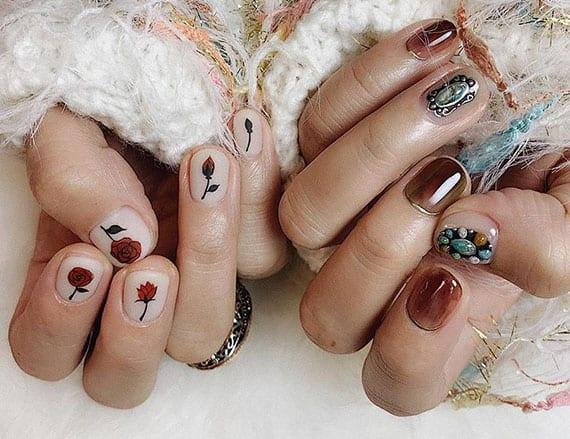 attraktive maniküre für kurze nägel in weiß mit rosen-auffkleber und boho-nagelgestaltung in gold und braun