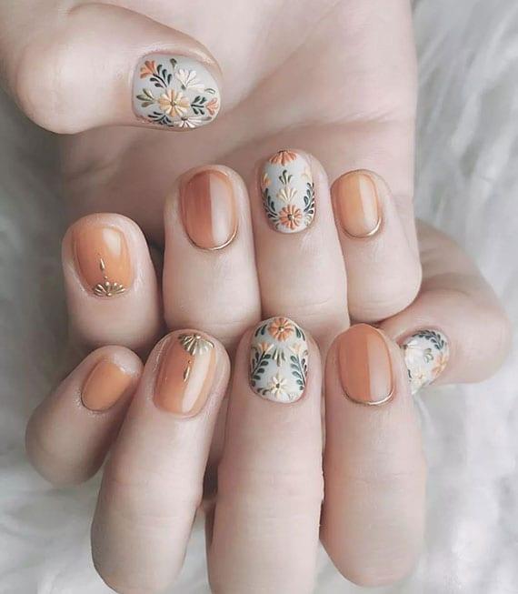 schöne maniküre für kurze nägel in orange und weiß mit blumen motiven