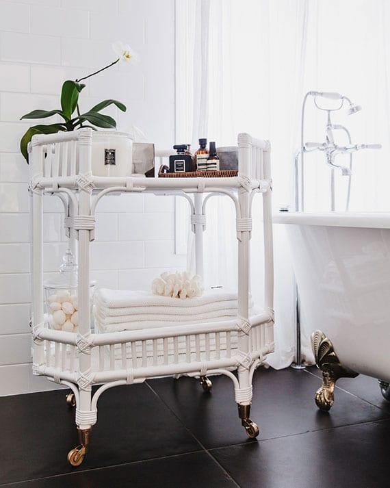 schöne bad idee mit schwarzen bodenfliesen, weißen Metro Fliesen, badewanne mit löwenfüßen und rustikalem rattantisch mit rollen in weiß
