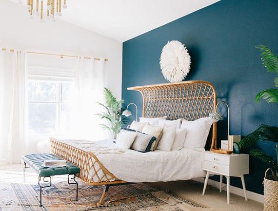 modernes schlafzimmer im boho stil mit blauer akzentwand, exotischem rattanbett, weißen nachttischen und ledersitzbank