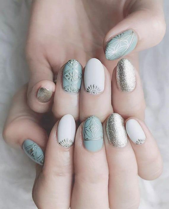 boho nail art für eine attraktive klassische maniküre in weiß, hellblau und silberglitzer