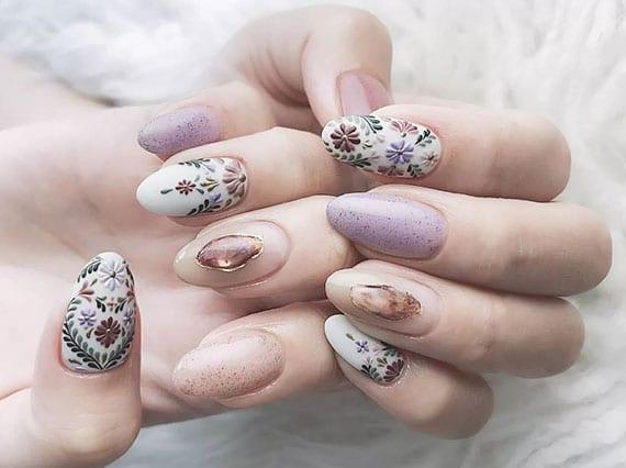 effektvole nagelgestaltung mit blumen, glitzer und zarten nagellackfarben