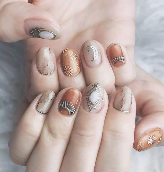 schöne maniküre in orange und nude farbe mit marmoreffekt, blumen und symbolen