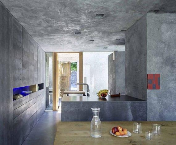 kleine offene küche mit essbereich, einbauküchenschränken in betonoptik, wandnische mit indirekter beleuchtung in blau und L-förmiger Kochinsel