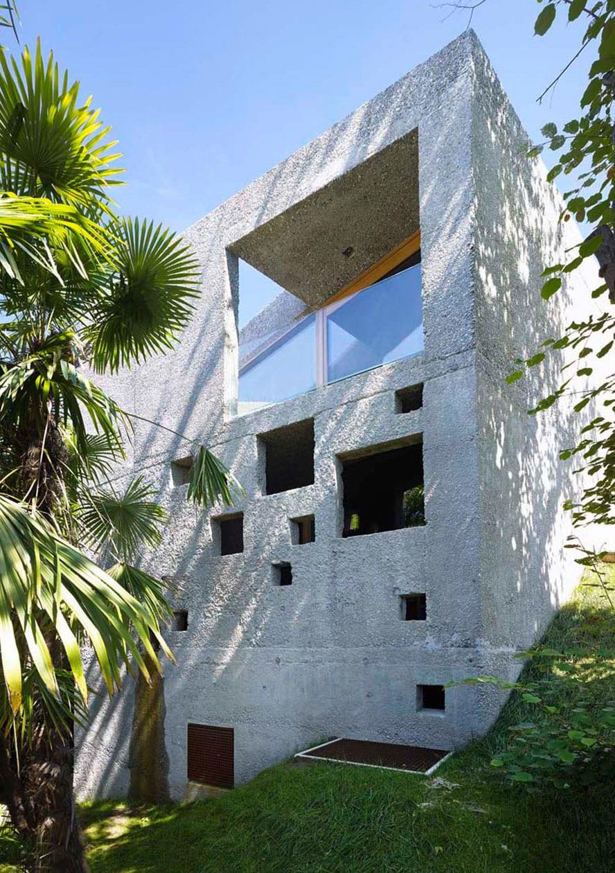 mehrgeschossiges gebäudevolumen aus beton mit attraktiver lochfassade und überdachter terrasse