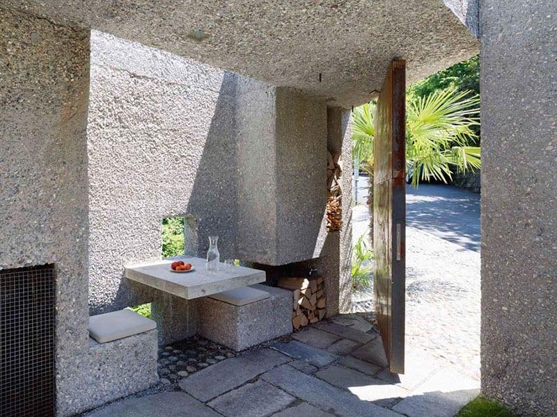modernes betonhaus mit kleinem eingangshof als emfangsbereich im freien mit kamin und ausgemauerter sitzecke