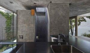 attraktives betonhaus mit polygonalen Außenform mit verglasung zu zwei begrünten innenhöfen und mit lochfassade zur spilerische raumbeleuchtung mit tageslicht