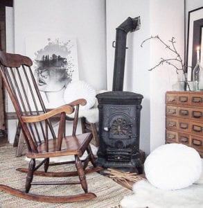 attraktives-interieur-design-im-skandinavischen-stil-für-gemütliche-wohnzimmergestaltung-mit-vintage-kaminofen-und-schaukelstuhl