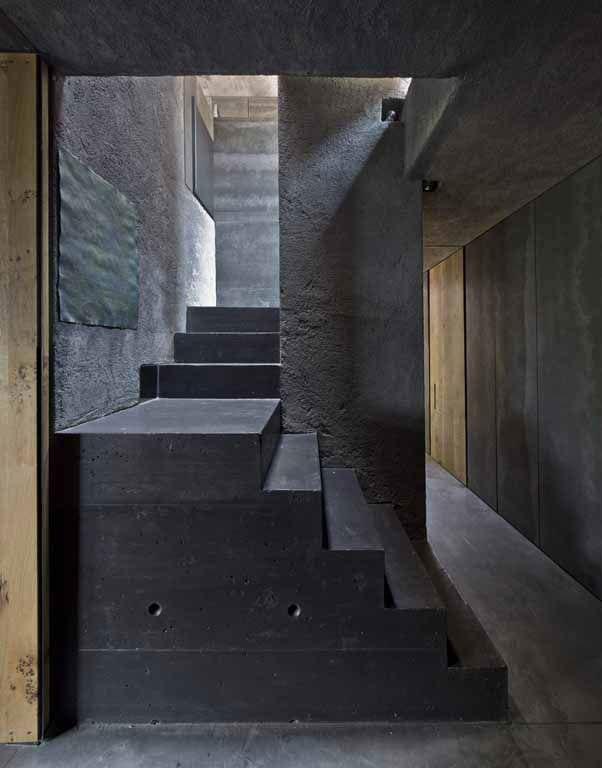 haus mit schlichtem interieur in dunkelgrau und schwarz, betonwänden, holztüren und offener innentreppe mit oberlicht