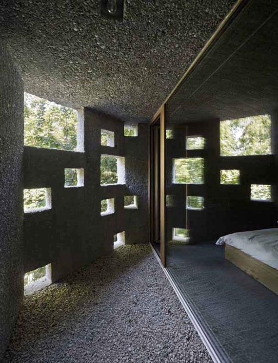 modernes schlafzimmer mit verglasung zur überdachte terrasse mit kiesboden und lochfassade