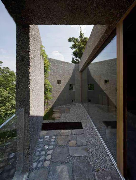 kleiner hofgarten mit wänden aus beton, naturstein-pflasterboden, begrünung und verglasung zum innenraum