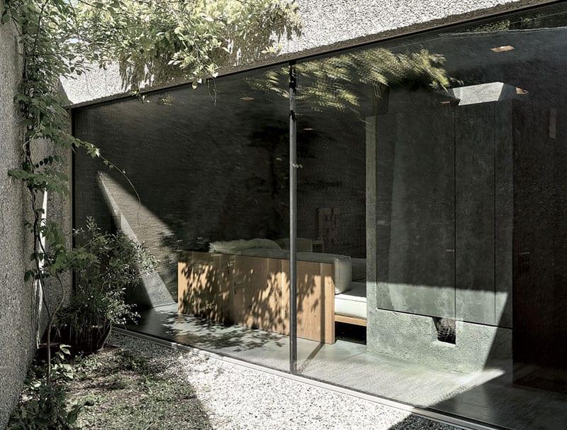 minimalistisches betonhaus mit panorama verglasung zum dreieckigem hofgarten mit betonmauer