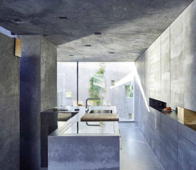 schlichte kleine einbauküche mit kochinsel aus beton, wetonwänden und panoramafenster zum kleinen hofgarten