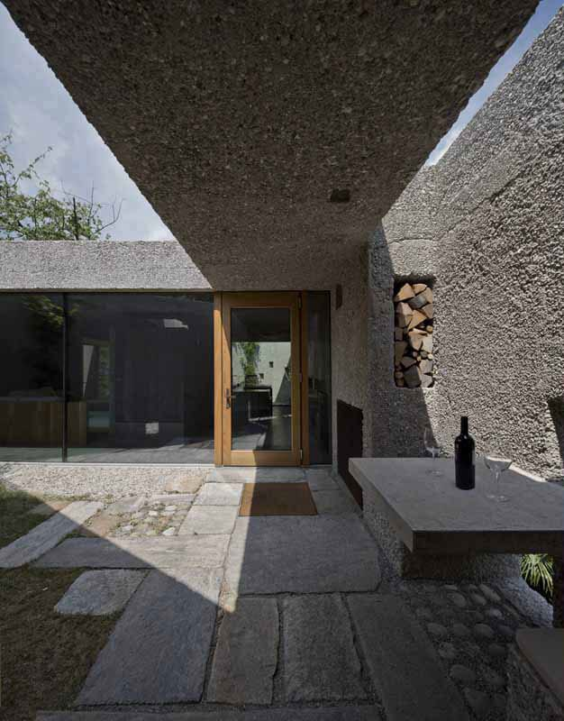coole idee für kleinen hofgarten mit wänden und überdachung aus beton, ausgemauerter sitzecke mit tisch aus beton und wandnischen mit kaminholz für einbaukamin