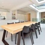 moderne wohnesszimmer mit weißer küche in hochglanz und rustikaler massibholzesstisch