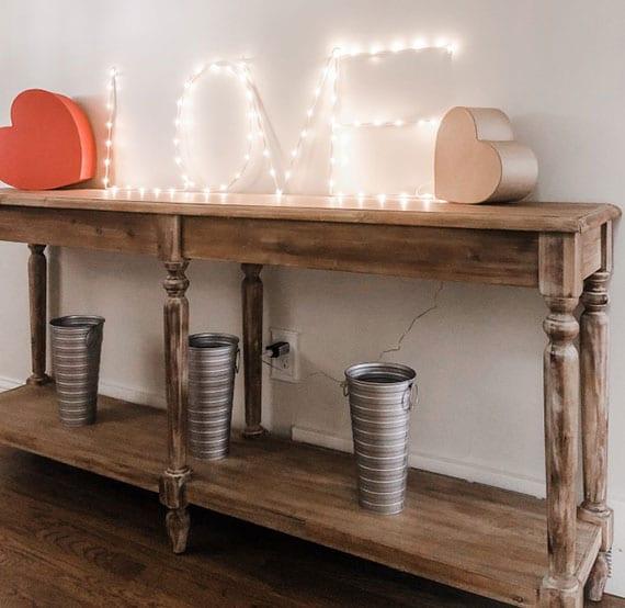 vintage sideboard aus holz kreativ dekorieren am teg der verliebten mit led-lichterkette-monogramm und roten geschenkboxen in herzform