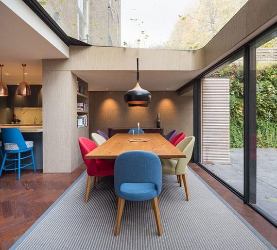 schöne wohnidee für attraktive, moderne und farbefröhe esszimmergestaltung durch essgruppe mit holzesstisch und farbigen polsterstühlen unter großem oberlicht