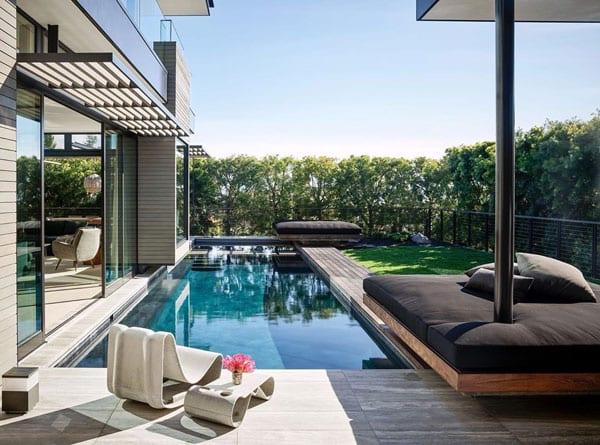 attraktive gartengestaltung mit überdachter sitzecke und ebenerdigem schwimmbecken direkt vor wohnzimmer mit schiebetüren