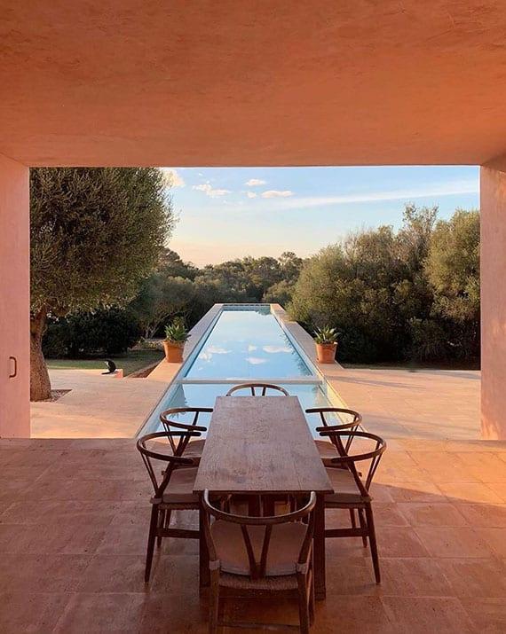 essbereich im außenbereich vom modernen haus im mediterranen stil mit überdachter terrasse und langem schwimmbecken