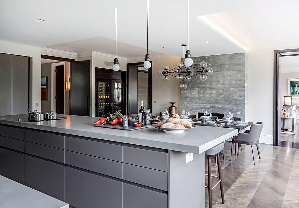 tolle wohnidee für moderne einbauküche in grau mit kochinsel und essbereich mit einbaukamin, akzentwand mit natursteinverkleidung und parkettboden