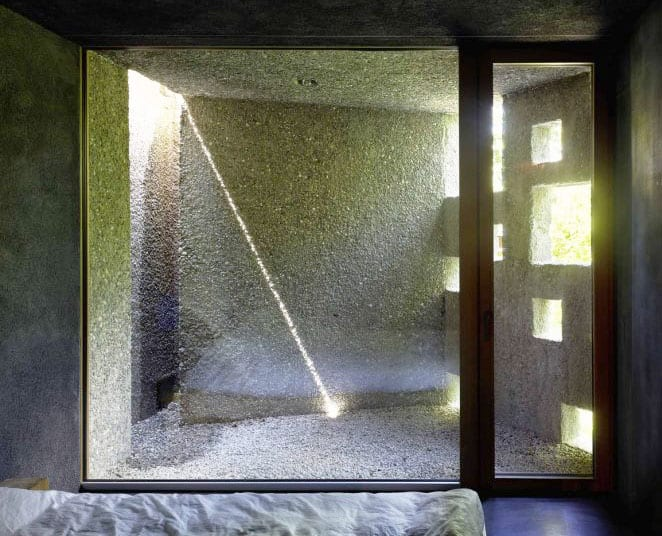 lichtgestaltung im schlafzimmer mit kleinem hofgarten aus betonwänden mit quadratischen öffnungen