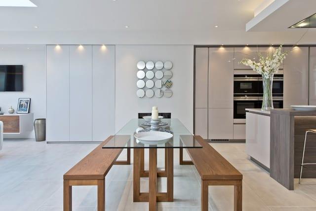 wohnesszimmer stilvoll und wohnlich einrichten mit einbauküche beige, einbaukamin, essgruppe mit holzbänken und glasesstisch, wanddeko mit runden spiegeln und indirekter deckenbeleuchtung