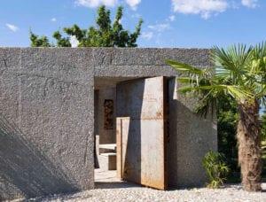 modernes-wohnhaus-mit-betonmauer-undeisentor-zur-straßenseite