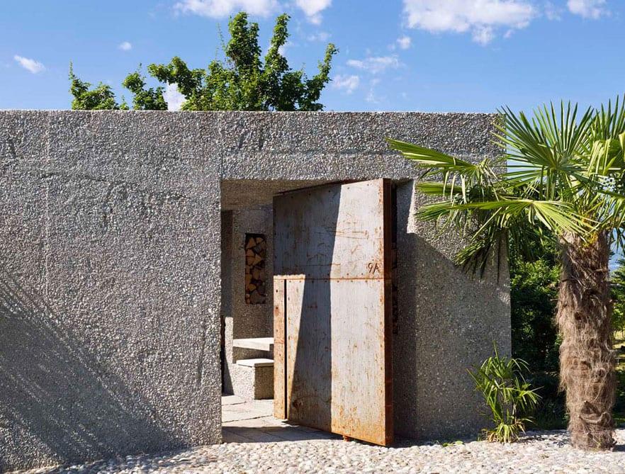 wohnhaus aus beton als eingeschossiges volumen mit dicker betonmauer und haustür aus metall