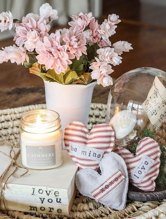 anleitung für diy herz-duftkissen mit trockenen blüten als rustikale romantische deko duftkerze, büchern, glasglocke und frischen blumen in keramikvase