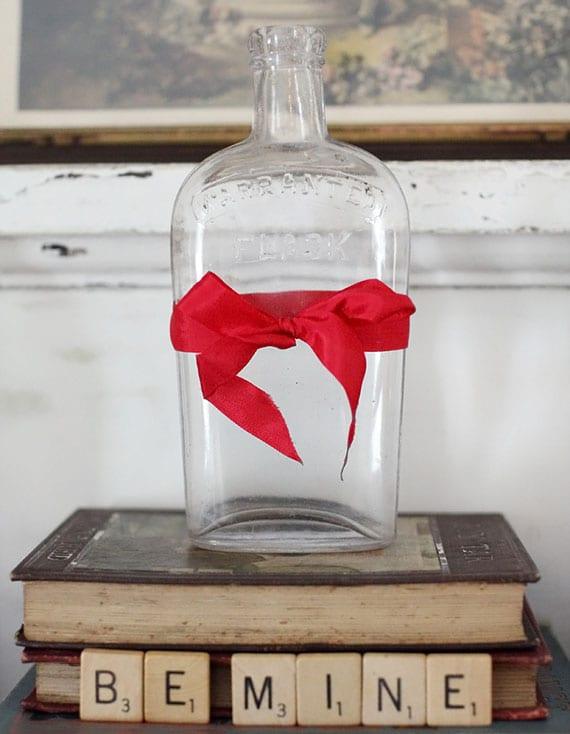 rustikale valentinstag deko mit alten büchern, alter glasflasche mit roter schleife und Scrabble Buchstaben