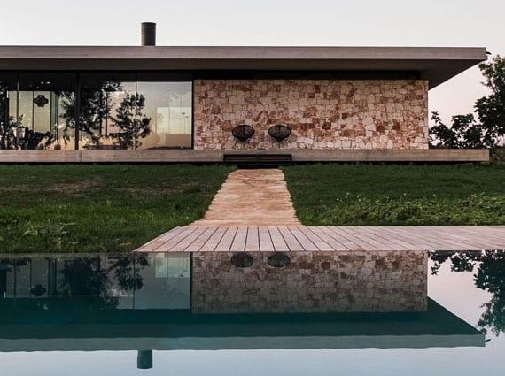 modernes eingeschoßiges haus aus beton mit bandverglasung, überdachte terrasse, wandverkleidung mit naturstein und gartenweg zum ebenerdigen schwimmbecken im garten