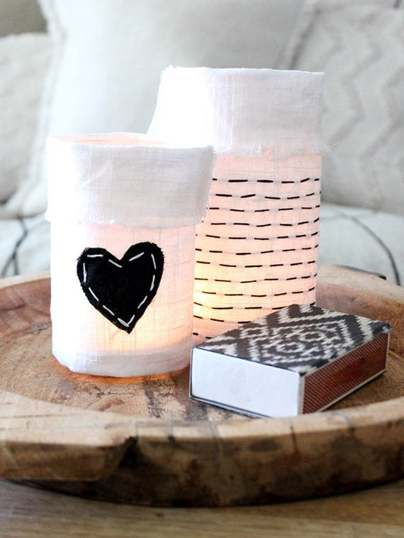 rustikale tischdeko mit glaswindlichtern in handbestickten Flaschenbezug aus weißem Leintuch in einer runden holzschale