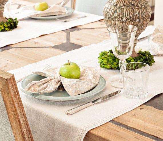 holzesstisch festlich eidecken und dekorieren mit leinen-tischläufer, tellern in hellblau, wasser- und weingläser, tellerdeko mit grünen äpfeln und stoffservietten