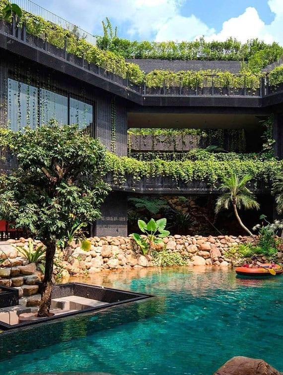 großzügiges einfamilienhaus mit schwimbecken und sitzecke im wasser als entapannungsort mit tropischer begrünung im mittig positioniereten hofgarten