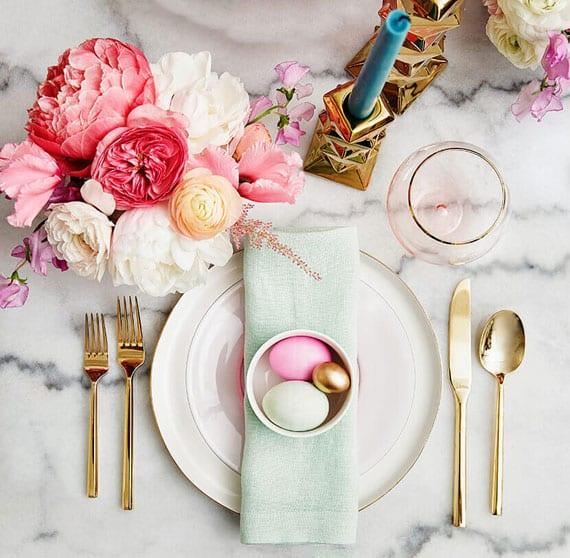 moderne tischdeko zu ostern mit blauen kerzen in goldenen kerzenhaltern, weißen und rosafarbigen rankulen, ostereier in pastellfarben als platzteller deko und besteck in gold