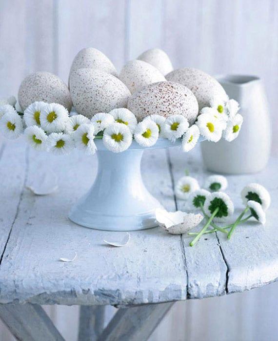 florale osterdekoration mit Gänseblümchen und gepunkteten weießen Ostereiern auf keramik tortenplatte