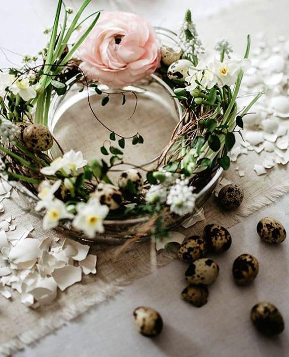 coole tischdeko ostern mit gebrochenen eierschalen und kranz aus frühlingsblüten in runder glasschale