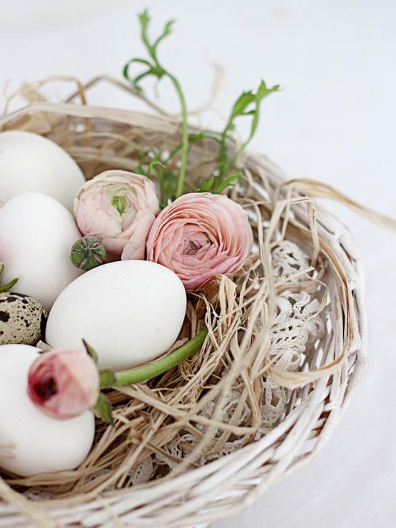 elegante osternest dekoidee mit weißen ostereiern, kleinen wachteleiern und rosafarbigen Ranunkeln in einem weidenkorb